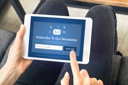 Subscribe to newsletter form on tablet computer screen to join list of susbscribers and receive exclusive offers and update. Digital communication marketing and email advertising. Membership sign-up