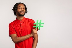 Subscribe to popular blog! Bearded man with dreadlocks wearing red casual style T-shirt, holding social media hashtag symbol and smiling. Indoor studio shot isolated on gray background.