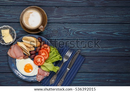 Shutterstock Substantial breakfast with fried egg, salad, bacon, bread and coffee, top view