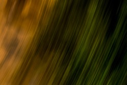 Subtle earthy blotchy orange light streaks alongside natural green light streaks and dark shadow areas - abstract diagonal motion blurred background / texture