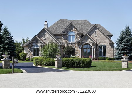 Suburban brick and stone home with cedar roof