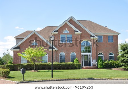 Suburban Brick Home in Residential Neighborhood - stock photo
