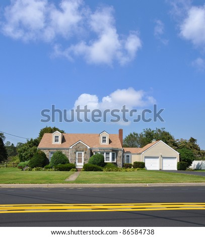 Suburban Bungalow Cottage Home in Residential Neighborhood on Two Lane Street with Yellow Traffic Line on Sunny Blue Sky Day