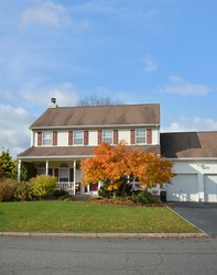 Suburban colonial style home fall autumn day residential neighborhood blue sky USA