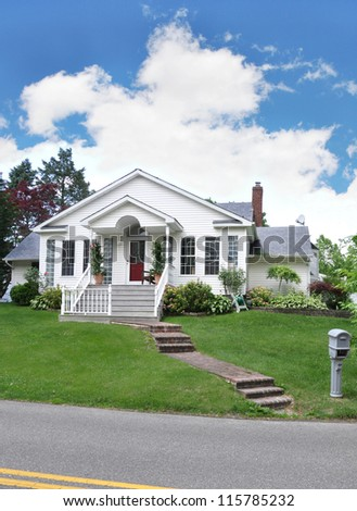 Suburban Cottage Home with Brick Steps Mailbox on curb of residential neighborhood street