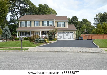 Suburban high ranch home with garage and blacktop driveway USA #688833877