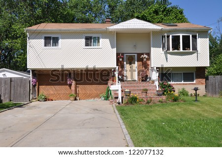 Suburban High Ranch Split Level Home front yard sunny blue sky day