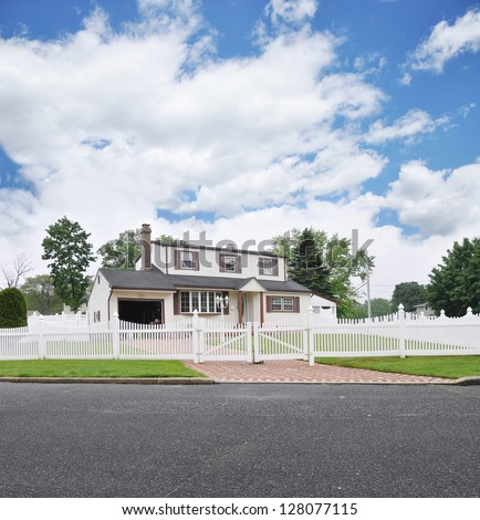 Suburban High Ranch White Picket Fence Brick Driveway Residential Neighborhood Street Blue Sky Clouds