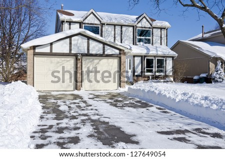 Suburban Home Covered with Snow on a Sunny Day