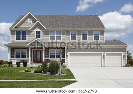 Suburban home with beige siding and double garage