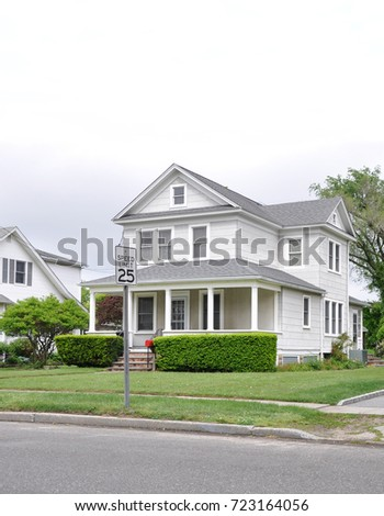 Suburban Home with porch overcast sky USA #723164056