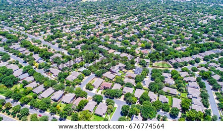 Suburban homes in Austin Texas USA aerial drone view during summertime green grass lush trees and endless houses and rooftops in the suburbs #676774564