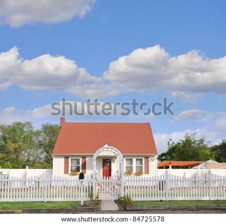 Suburban Middle Class Country Bungalow Cottage Home with White Picket Fence Beautiful Blue Cloudy Sky