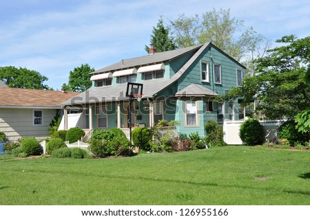 Suburban Neighborhood Cape Code Style Home with Basketball Hoop on Landscaped Front Yard Lawn Sunny Blue Sky Day