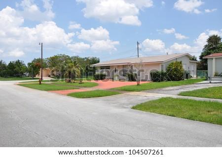Suburban Neighborhood Street Ranch Style Home sunny blue sky day clouds