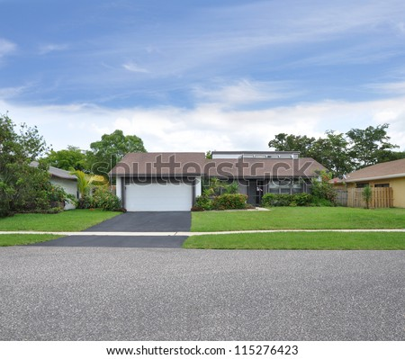 Suburban Ranch Style Home Blacktop Driveway One Car Garage landscaped Front Yard Lawn - stock photo