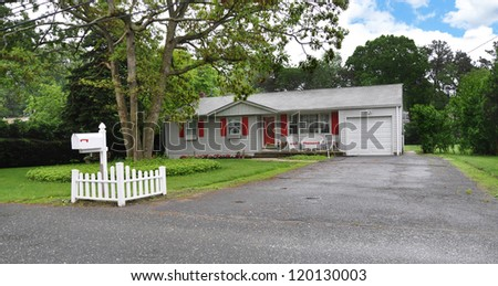 Suburban Ranch Style Home with Red Shutters wet blacktop driveway