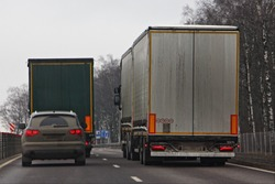 Suburban road traffic, a car in a hurry to overtake slow trucks in the left lane