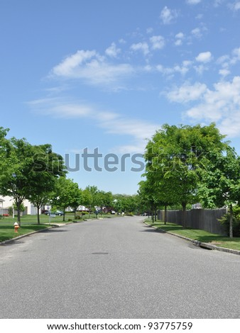 Suburban Street in Residential District Neighborhood under sunny blue sky - Shutterstock ID 93775759