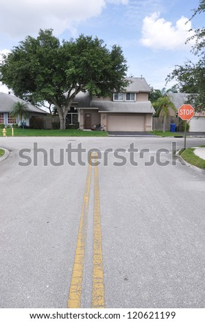 Suburban Street Stop Sign Home Snout Back Split Architecture Residential Neighborhood Blue Sky Clouds - stock photo