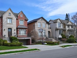 Suburban street with large detached houses with gables