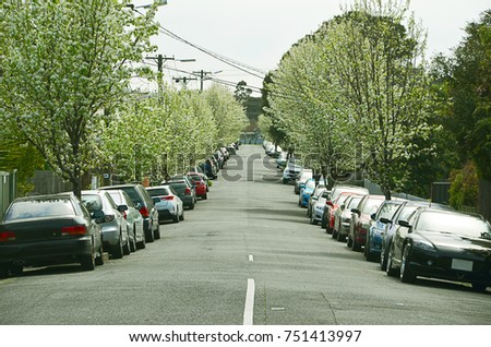 Suburban street with many cars parked in line on both sides of the road. Footscray, Victoria, Australia