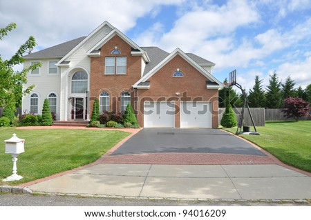 Suburban Two Car Garage  Blacktop Driveway with Basketball Hoop of Brick Home in residential suburban neighborhood