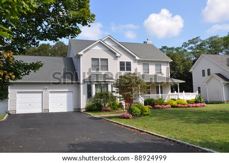 Suburban Two Car Garage Large Siding Home with Double Wide Blacktop Driveway Front Yard on Sunny Blue Sky Cloud Day #88924999