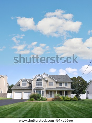 Suburban Two Car Garage Two Story Home Green Lawn Blue Cloud Sky McMansion style Architecture
