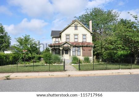 Suburban Victorian Home in residential neighborhood sunny blue sky day