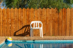 suburban villa back yard of swimming pool privacy space for spending free time for rest with ball on water surface and white plastic chair on wooden fence background
