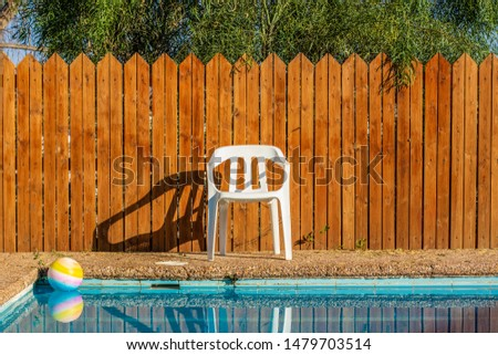 suburban villa back yard of swimming pool privacy space for spending free time for rest with ball on water surface and white plastic chair on wooden fence background  #1479703514