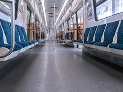 Subway car interior with colorful seats with no passengers in background. Empty interior inside of public transport train or metro in Saint Petersburg, Russian Federation