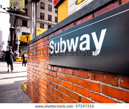 Subway entrance sign at a typical New York City intersection