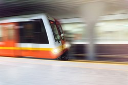 Subway passing by metro platform very fast. High speed train in underground tunnel. Public transportation concept with motion blur.