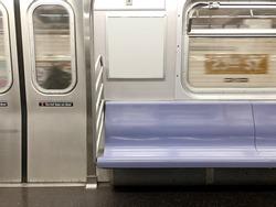 Subway seats and blank billboard