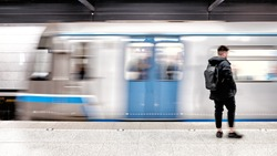 subway train arriving to modern metro station with male passenger person waiting on platform blurred background side view of city transportation underground station with motion car and people