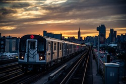 Subway train in New York at sunset and Manhattan cityscape view