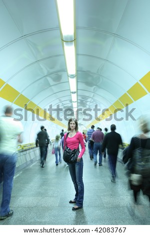 Subway - young woman standing in a subway corridor while the crowd of commuters passes by