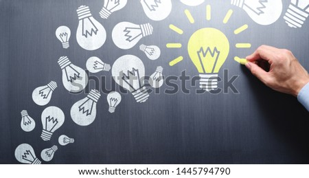 Succeed in finding solution after try and failure. Businessman drawing lightbulbs on chalkboard. #1445794790