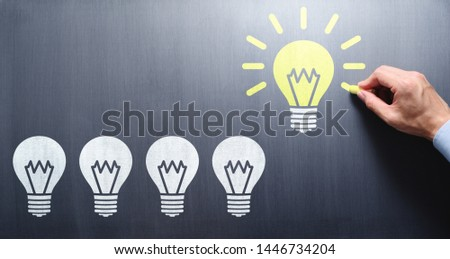 Succeed in finding solution. Businessman drawing lightbulbs on chalkboard. #1446734204