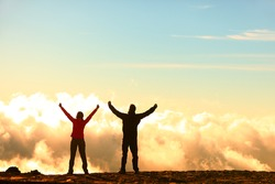 Success, achievement and accomplishment concept with hiking people cheering and celebrating of joy with arms raised outstretched up in the sky on trekking hike outside. Hikers having fun at sunset.
