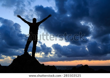 Success achievement silhouette, accomplish hiking accomplishment business concept with man celebrating with arms up raised outstretched faith worship outdoors
