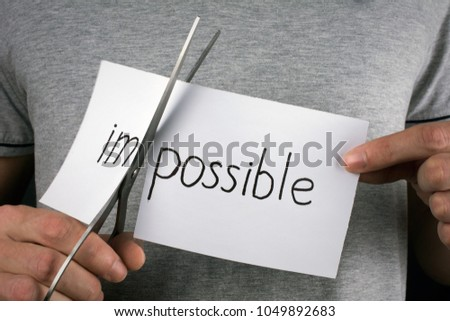 success and challenge concept. card with the text impossible, cutting the word im so it written possible.