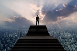Success and leader concept, businessman in suit standing on top of stair and looking over city with sun light
