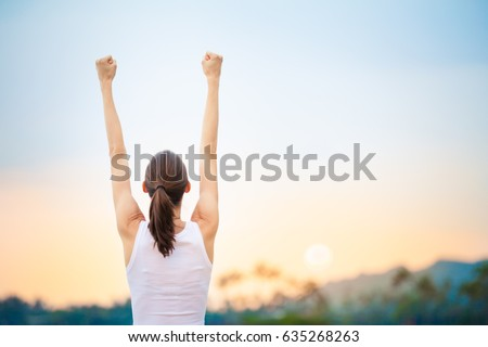 Success and life goals concept. Strong and confident woman with arms in the air.