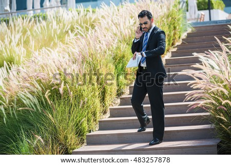 Success arabic businessman staying on stairs in front of office. Manager in formal suit talking by phone and holding business newspaper.
