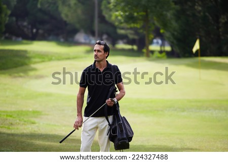 Success attractive man playing golf at leisure on holidays, success and welfare concept, handsome wealthy man in polo t-shirt standing on golf course, male golf player at the course with a club sack