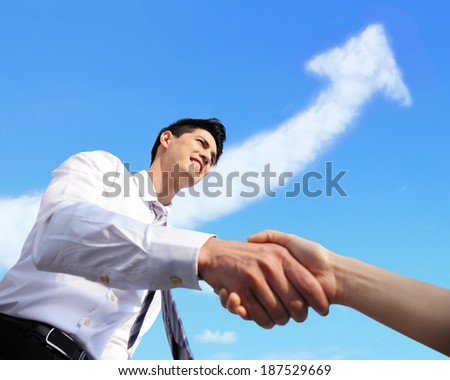Success Business concept - Business man handshake with arrow cloud and sky in the background