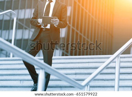 Success business man using tablet phone. Blue Toned Image. Concept businessman lifestyle.